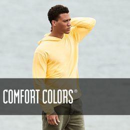 Healthy male model stud standing by the sea in his lemon hooded tee